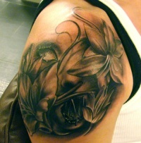Face and flowers tattoo on arm